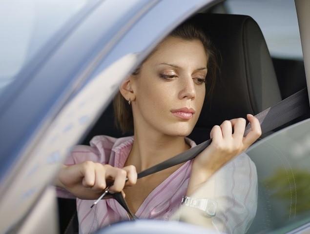 woman in car fastening safety belt